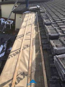 The relaying of the roof tiles after repairs